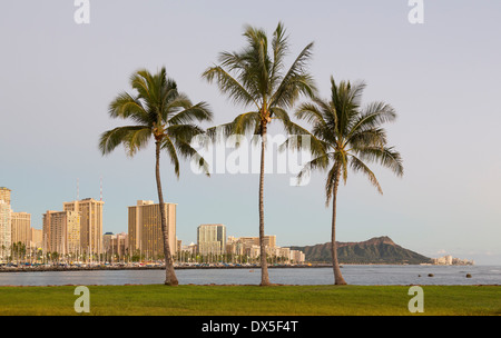 Honolulu and Waikiki from Ala Moana park as the sun sets with three palm trees, Hawaii, USA - Stock Photo