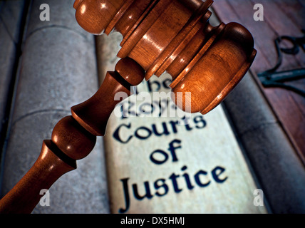 Law / Justice concept Close view on Judges gavel with entrance sign to Royal Courts of Justice Holborn London UK - Stock Photo