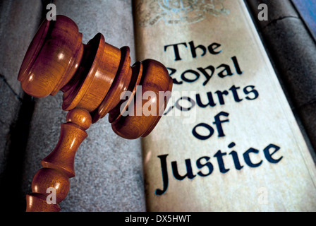 Law / Justice concept Close view on Judges gavel with entrance sign to Royal Courts of Justice London UK - Stock Photo
