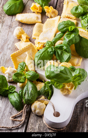 Homemade pasta ravioli and perle on old wooden table with fresh basil - Stock Photo
