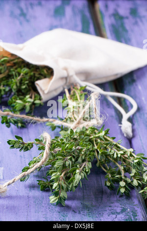 Bunch of fresh thyme and thyme in textile bag on violet wooden table - Stock Photo