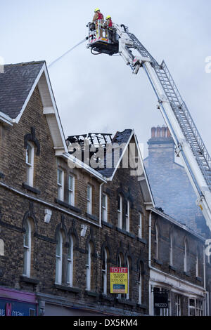 Brave firefighter crew (2 firefighters) up high ladder, tackle fire with water hose at town centre building - Harrogate, - Stock Photo