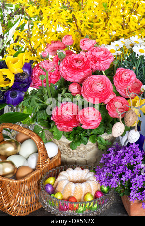 fresh spring flowers with easter cake and eggs decoration. ranunculus, campanula, forsythia, tulips, anemone - Stock Photo