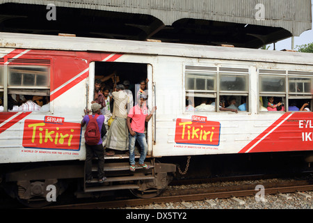 People hanging from open doors of commuter train passing through Mount Lavinia railway station in Colombo - Stock Photo
