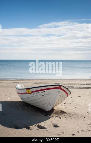 Boat drawn up on the beach at Estepona on Spain's Mediterranean coast. - Stock Photo