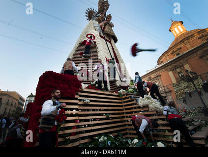 Valencia, Spain. 18th Mar, 2014. People decorate the giant sculpture of the Virgin with flowers during the Fallas - Stock Photo