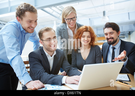 Image of a young business team working out strategy together - Stock Photo