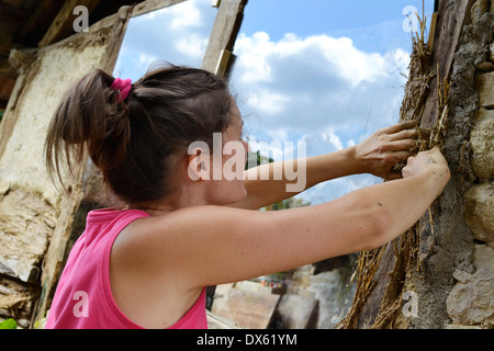 Young female plastering a old stone building with natural materials - clay, sand and straw. - Stock Photo