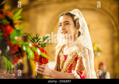 Valencia, Spain. March 18th, 2014: A young Fallera finally offers her flower bouquet to the Virgin and hands it - Stock Photo
