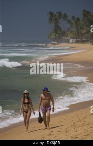 Couple walking along Hikkaduwa Beach, Sri Lanka - Stock Photo
