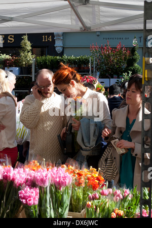 A couple shopping for tulips in Columbia Road Flower Market on a sunny March weekend in East London E2 England UK - Stock Photo