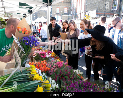 Woman in black buying spring tulips from bulb cut flowers seller in Columbia Road Flower Market East London E2 England - Stock Photo