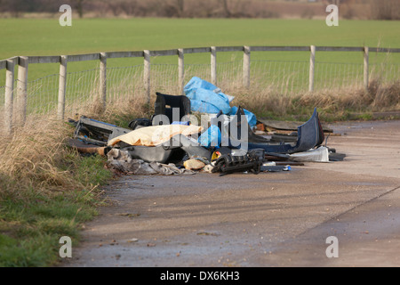 Flytipped car parts and other debris in a layby next to farmland. - Stock Photo