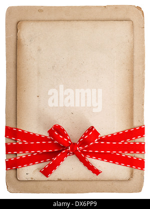 vintage card with red ribbon bow isolated on white. grunge paper background - Stock Photo