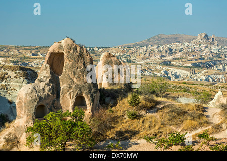 Dwellings in fairy chimneys and Uchisar (R) in distance, Red Valley, Cappadocia, Turkey - Stock Photo