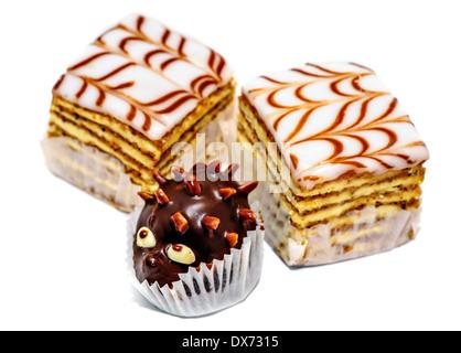 Layered cakes and chocolate hedgehog isolated on white background - Stock Photo
