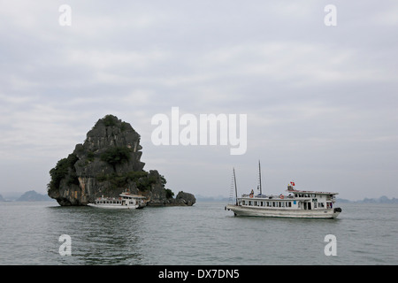 Tour boats in Ha Long Bay surrounded by  limestone karst formations.  Vietnam, Southeast Asia - Stock Photo