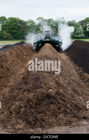 Komptech self propelled compost turner, turning over rotting bedding manure. - Stock Photo
