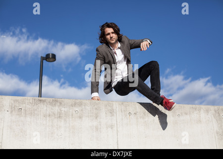 A young male model on a concrete wall with blue sky behind - Stock Photo