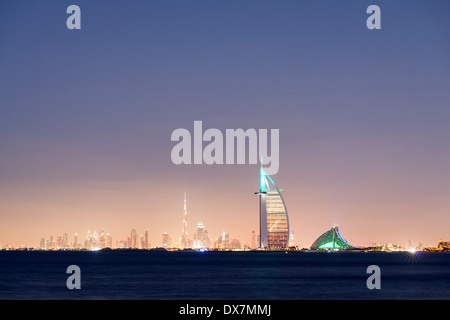 Night skyline across sea to luxury Burj al Arab hotel and city of Dubai with Burj Khalifa tower in distance United - Stock Photo