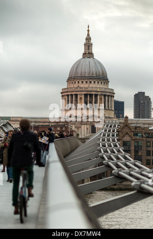 A cyclist and pedestians on the Millennium Bridge looking towards St Paul's Cathedra,l London - Stock Photo