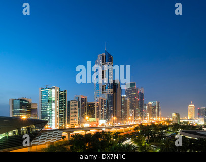 Dusk view of skyline of skyscrapers along Sheikh Zayed Road in Dubai United Arab Emirates - Stock Photo
