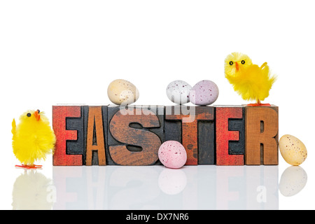 The word Easter in old wooden letterpress with a toy chicks and candy covered chocolate eggs, isolated on a white - Stock Photo