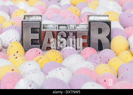 The word Easter in old metal letterpress surrounded by candy covered mini chocolate eggs. - Stock Photo