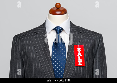 Front view of a Mens grey wool pinstripe suit jacket with blue tie and white shirt on a tailors dummy - Stock Photo
