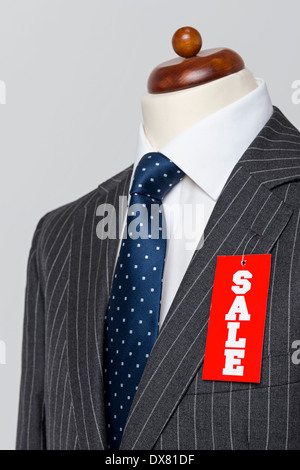 Side view Mens grey wool pinstripe suit jacket with blue tie and white shirt on a tailors dummy - Stock Photo