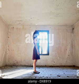 Woman standing by the window - Stock Photo