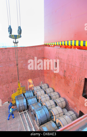 Coiled steel sheets being loaded in a ship - Stock Photo