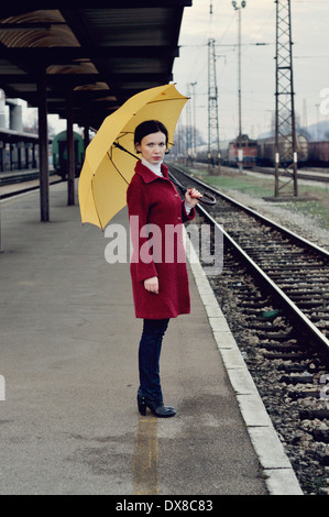 Mid adult woman standing on railroad station platform holding umbrella - Stock Photo