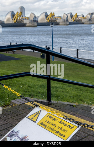 Danger - keep out: a sign at the Thames Flood Barrier warns of the danger of flooding. Shown here in the raised - Stock Photo