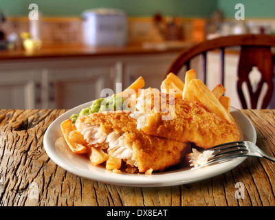 Traditional British  Battered Fish And Chips served on a plate in a traditional kitchen setting ready to eat - Stock Photo