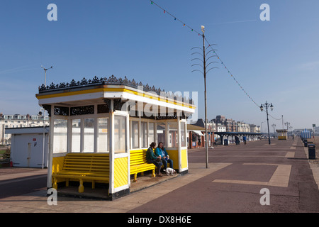 People resting in a promenade shelter at Southsea. - Stock Photo