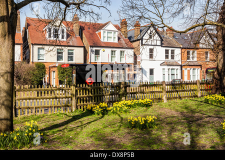 Row Of Traditional English Houses With Attic Room Bus Stop And Daffodils In Park