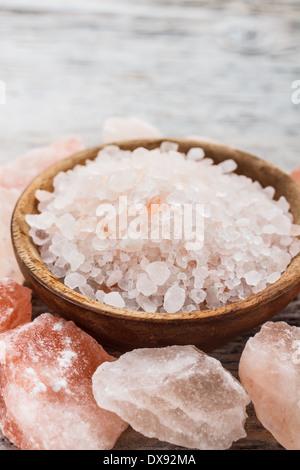Himalayan pink salt in wooden bowl - Stock Photo
