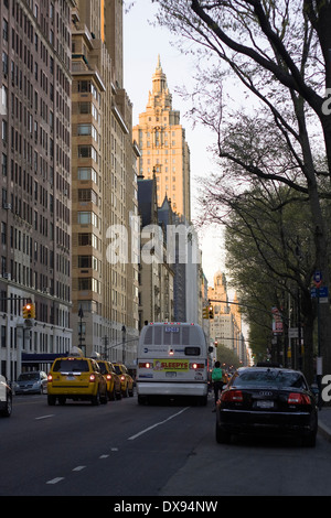 An MTA Bus and a line of Taxi Cabs travel North past parked cars on New York's Central Park West at 70th Street - Stock Photo