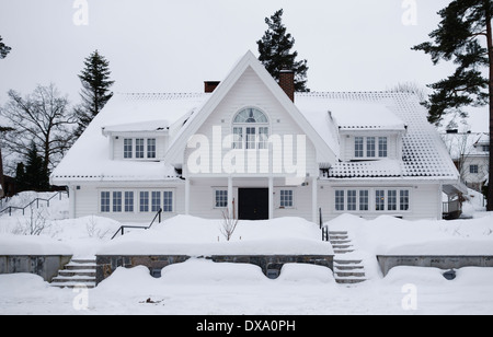 A snow covered white wooden house in a suburb of Oslo, Norway - Stock Photo
