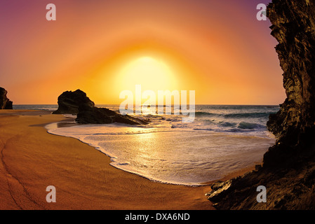 Portugal, Alentejo: Romantic sunset at rocky beach in Porto Covo - Stock Photo