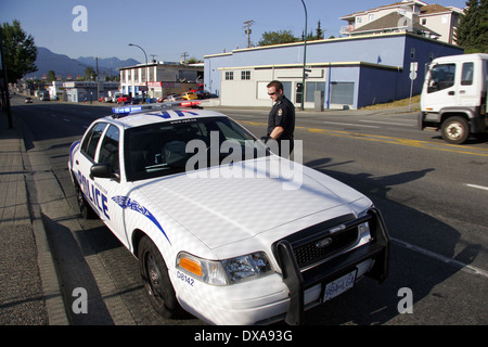 A Vancouver Police Department cop at his car, Vancouver, British Columbia, Canada - Stock Photo