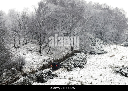 Snow cover forest track near Sherrifmuir, Stirling, Scotland. A 4x4 car be seen driving on the road. - Stock Photo