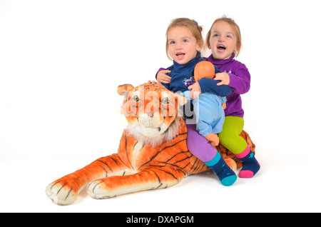 Twins having Fun playing and riding a Tiger - Stock Photo