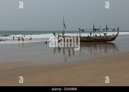 Children playing in fishing boat and in the sea at Kokrobite Beach, Ghana - Stock Photo