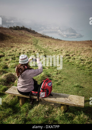 A woman taking a photograph of Ilfracombe harbor as the morning mist starts to lift - Stock Photo
