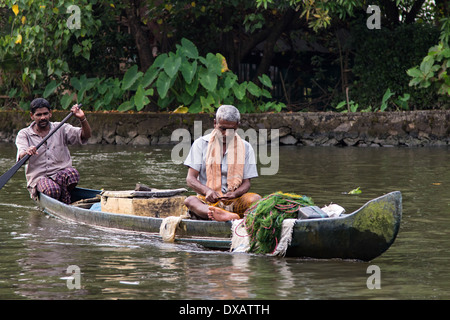 Fishermen in a canoe on the river in the Alleppey backwaters in Kerala, India - Stock Photo
