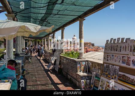 Tourists enjoying views of Alfama and Igreja de Santa Engrácia from Miradouro de Santa Luzia, in Alfama, Lisbon, - Stock Photo