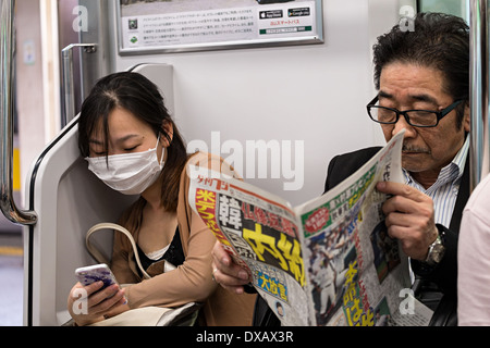 Japanese man reading newspaper and Japanese woman commuter with face mask reading mobile phone in Tokyo metro train, - Stock Photo