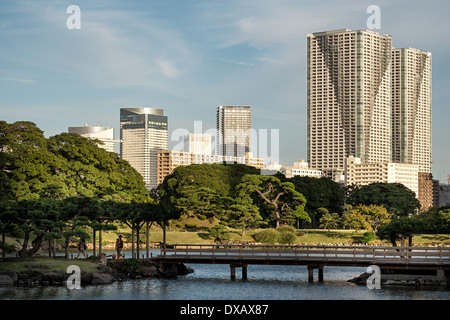 Bridge in Hama-rikyu Gardens with Shiodome skyscrapers in the background, Tokyo, Japan - Stock Photo